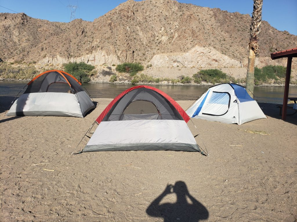 Three tents at a campsite by a river