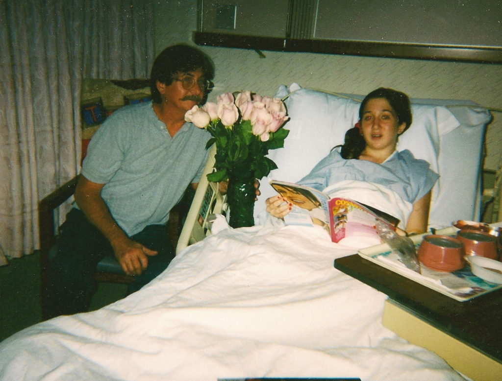 Girl in a hospital bed with her dad sitting besides her