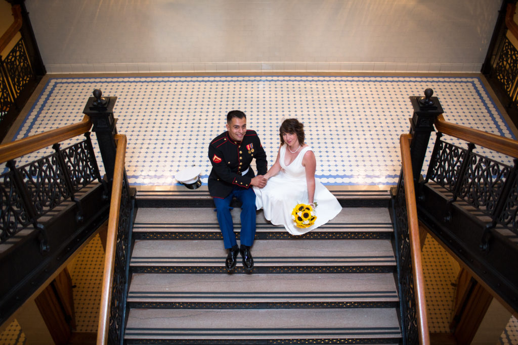 Marine and Bride sit in a stairwell