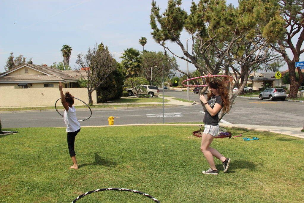 Aunt and young niece hula hoop