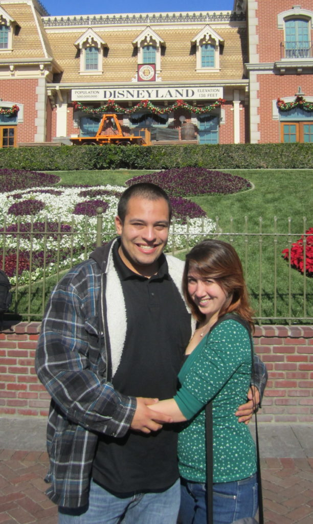 Couple stand at the entrance to Disneyland