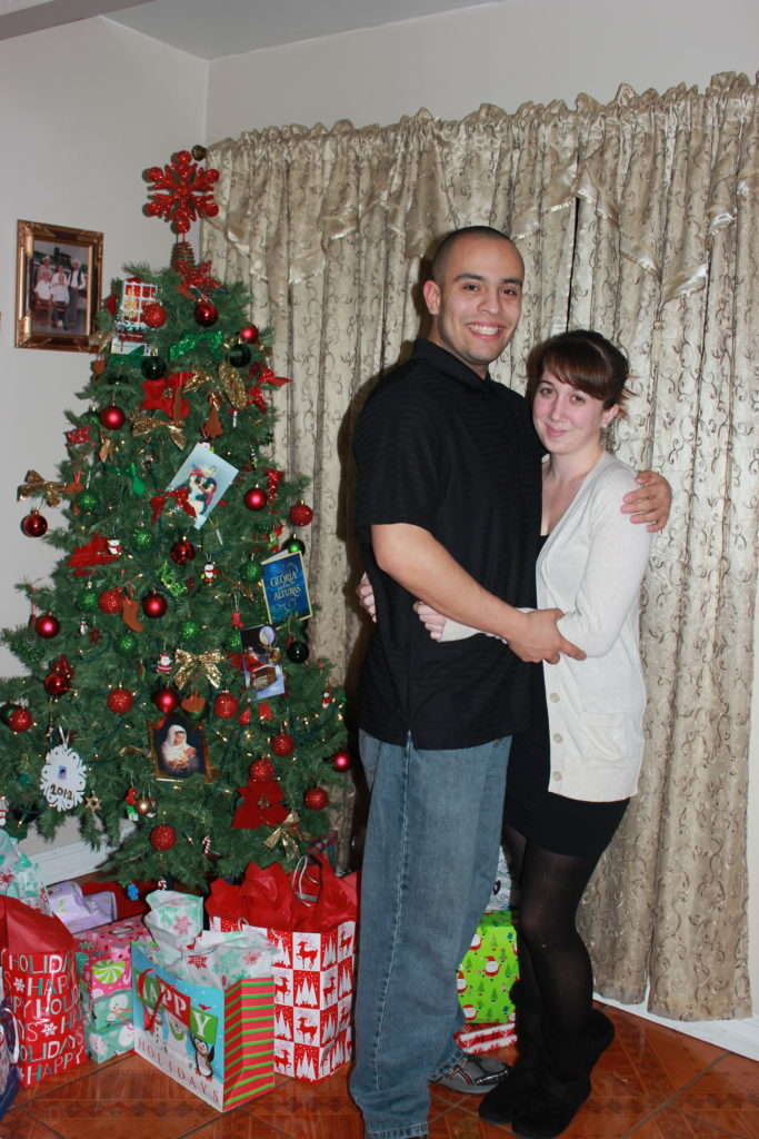 Couple stands in front of a Christmas Tree