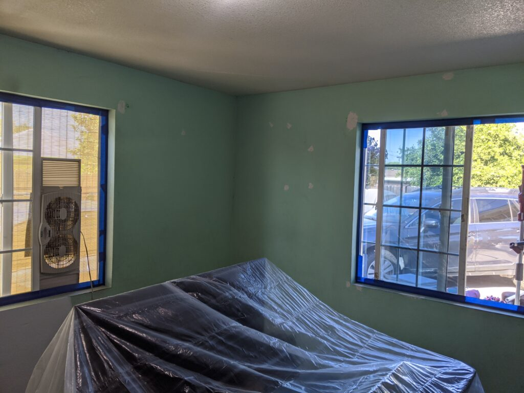 Turquoise living room prepped to be painted
