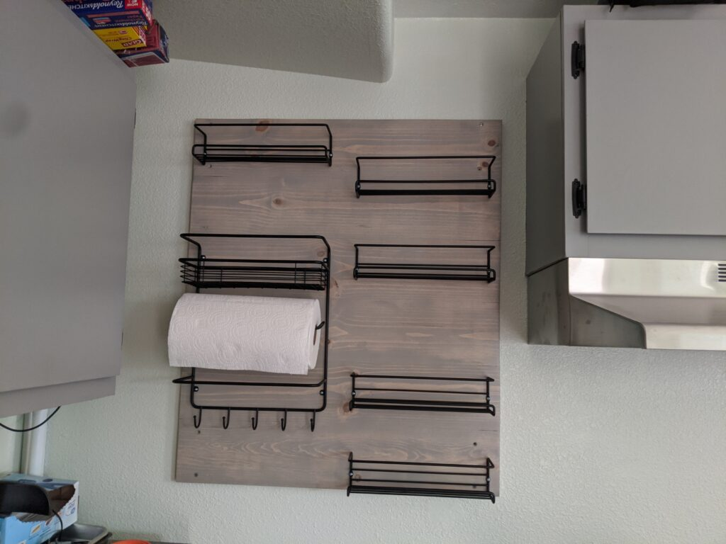 Wooden panel with black metal spice racks