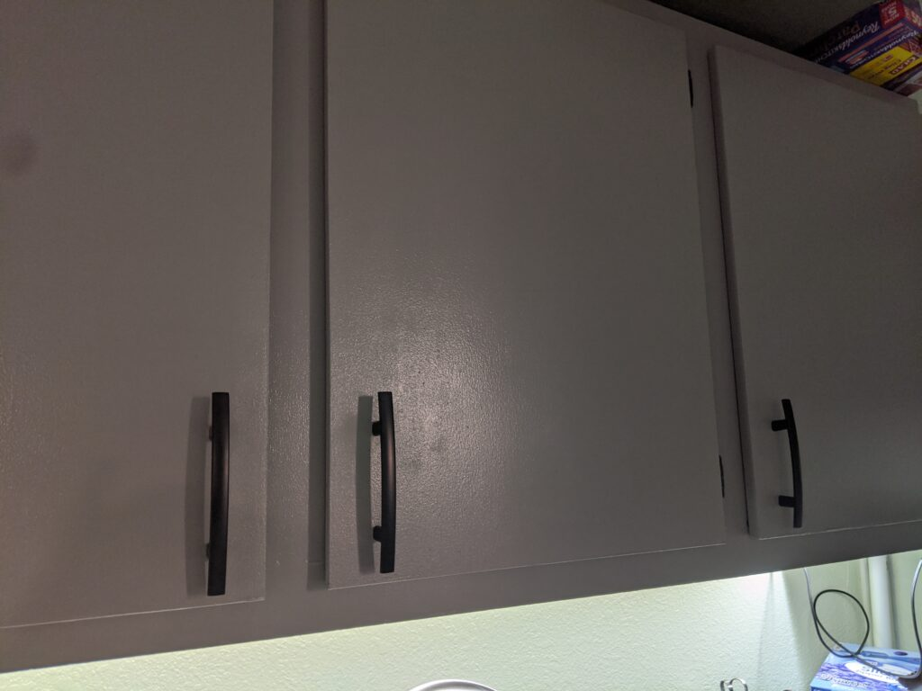 Grey kitchen cabinets with black handles